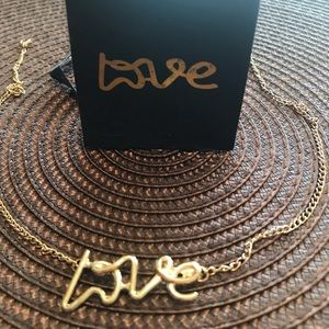 """Jewelry - Gold colored """"Love"""" necklace."""